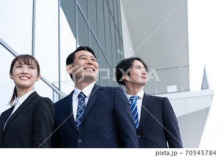 ビルの前で立つ3人の笑顔のビジネスパーソン 70545784