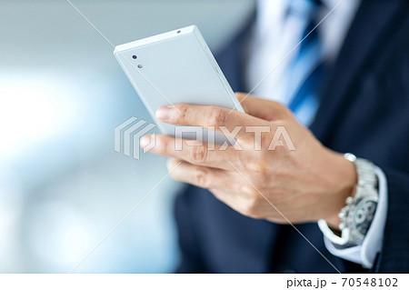 スマホを操作するビジネスマンの手元イメージ 70548102