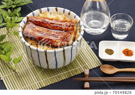 竹マットに置いた鰻丼とガラス器の日本酒 70549826