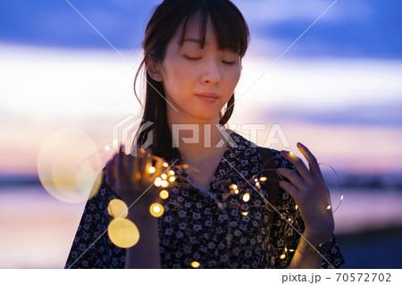 イルミネーションライトを見つめる若い女性 70572702