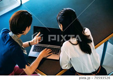 オフィスでパソコンを使いながらミーティングする2人のビジネスウーマン(カジュアル) 70593526