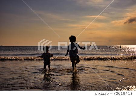 夕方の海の波打ち際で遊ぶ小さな兄弟 70619413