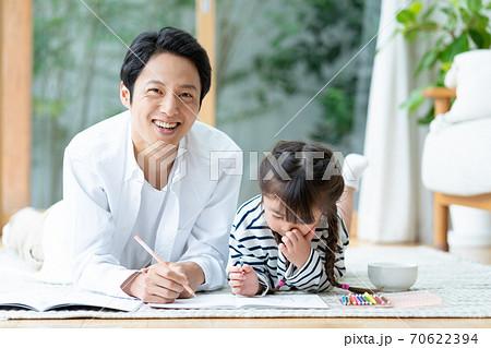 寝転んでお絵描きをする女の子とパパ 70622394
