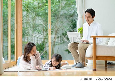 寝転んでお絵描きをする女の子とママを仕事をしながら見守るパパ 70625928