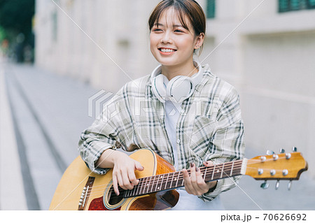 woman playing guitar on the street 70626692