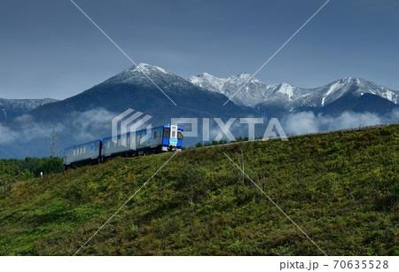 北杜市小淵沢町、八ヶ岳に初雪が降った朝の小海線上り回送列車 70635528