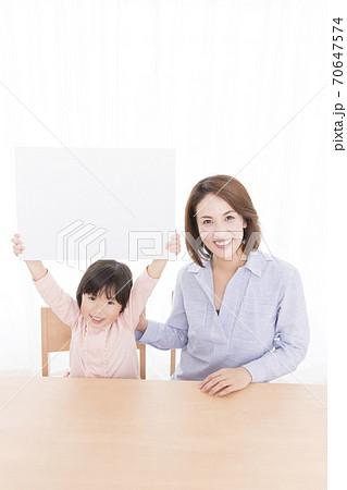 メッセージボードを持つ親子 70647574