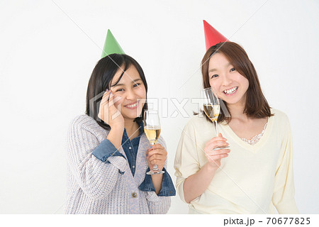 シャンパングラスを片手に微笑む三角帽子を被った若い女性2人(上半身) 70677825