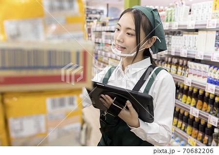 スーパーで在庫管理をするマウスシールドをした女性従業員 70682206