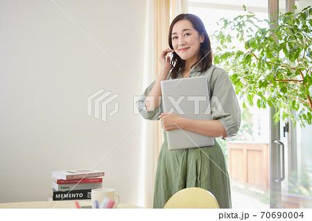 リビングでパソコンを持って立っている女性 70690004