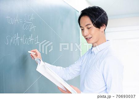黒板に数式を書く笑顔の若い男性教師 70693037