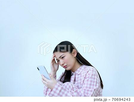 パジャマ姿でスマートフォンを操作する女性イメージ 70694243