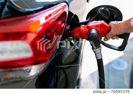 ガソリンスタンドで給油をする男性 70695376