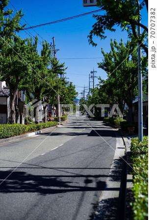 蛇行する緩やかな坂道のある住宅街、早朝の青空広がる風景 70707382
