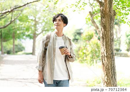コーヒーを飲みながら散歩する男性 70712364