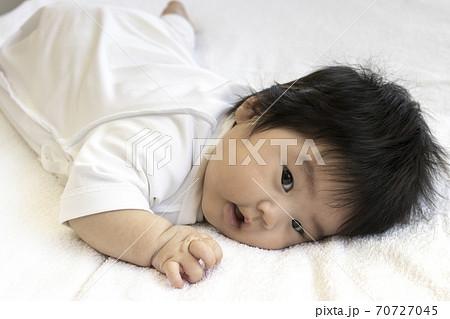 うつ伏せの生後3ヶ月の赤ちゃん、カメラ目線 70727045