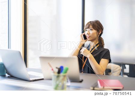 仕事中に同僚からの電話がかかってきてリラックスして電話対応しているビジネスパーソン  70750541