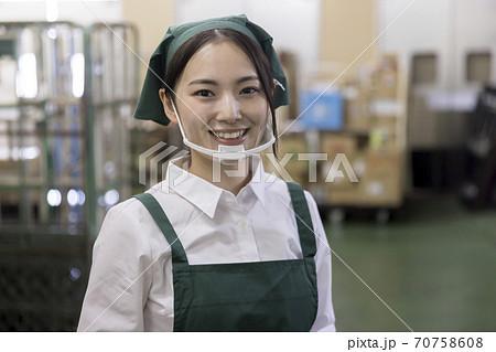 スーパーのバックヤードでマウスシールドをしたカメラ目線女性従業員 70758608