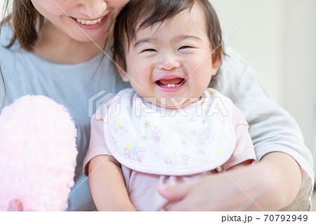 お母さんに抱っこされてご機嫌の赤ちゃんの顔のアップ 70792949