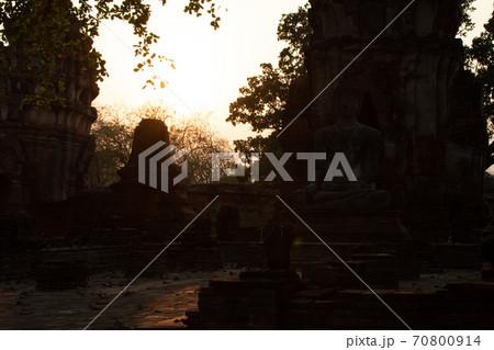 タイのアユタヤにあるワット・マハータートで見た、背後から夕陽を浴びる仏塔や仏像のシルエット 70800914