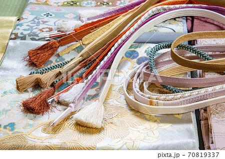 袋帯の上に置いたたくさんの帯締め 70819337