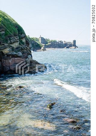 スコットランド郊外にあるセントアンドリュースの岩場の海岸と遠くに見えるセントアンドリュース城 70825032