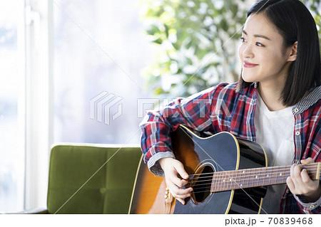 ギターを弾く若い女性 70839468