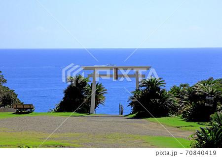 都井岬の先端に建立された御崎神社の鳥居の上を走る漁船 70840419