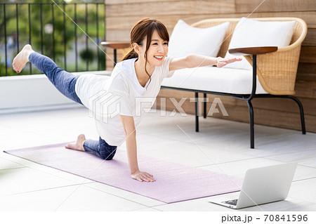 バルコニーでオンラインヨガをする若い女性 70841596