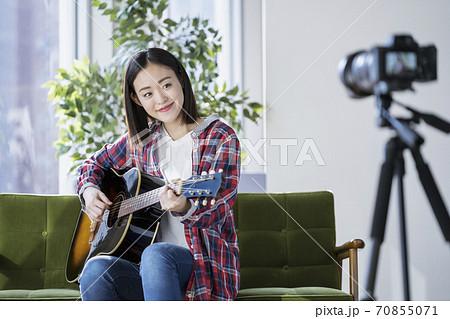 ギターを持って動画撮影をする女性 ライブ配信をするミュージシャン イメージ 70855071
