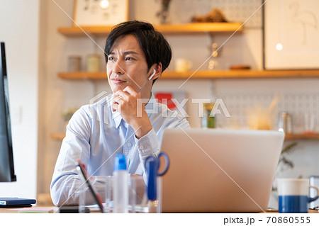 テレワーク 自宅のリビングでweb会議をする困った顔の若い男性 70860555