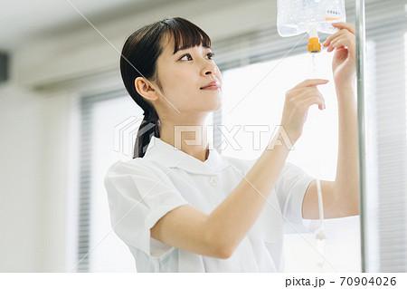 点滴の準備をする女性看護師 70904026