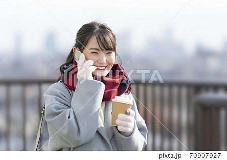 スマートフォンで通話する笑顔の若い女性 70907927