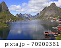 Sharp mountains, red huts and fishing boats reflected into the fjord in Reine, Lofoten Islands, Norway  70909361