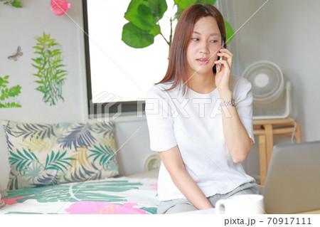 テレワーク_電話しながら「えっ何それ」という表情の女性 70917111