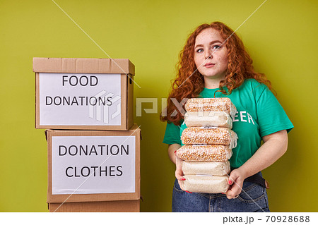beautiful redhead volunteer woman collecting donation for poor 70928688