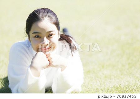 芝生で寛ぐ笑顔の若い女性カメラ目線 70937455
