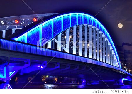 満月の夜に青く光る隅田川に架かる永代橋 70939332