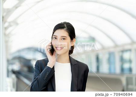 スマホで通話するビジネスウーマン【屋外】 70940694