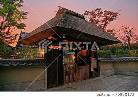 夕照に浮かび上がる茅葺き屋根の山門 70950172