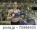 Woman Running on Treadmill 70966435