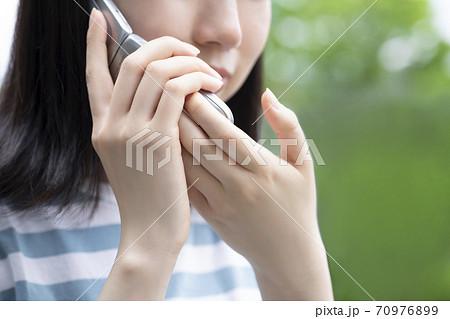 ガラケーで小声で電話をする女性 70976899