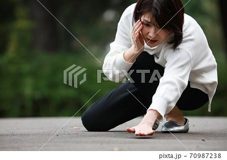 コンタクトレンズを落とした女性 70987238
