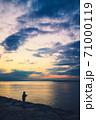 マジックアワーを幻想的に表現した、堤防から海を望む釣り人の写真 71000119