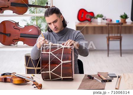 Young male repairman repairing drum 71006314