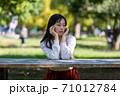 公園のベンチに座り頬杖をつく長い髪の女性 71012784