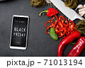 Modern smartphone with black friday banner on the screen lies on countertop with spicy vegetables 71013194