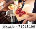 Male hand drops freshly sliced meat into a pot of water 71013199