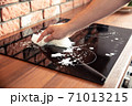 Man hand cleaning a induction cooker with some cleaning detergent 71013215