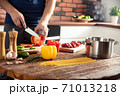 Man preparing delicious and healthy food in the home kitchen 71013218